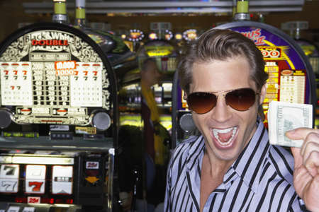 Young man holding his winnings at the casino