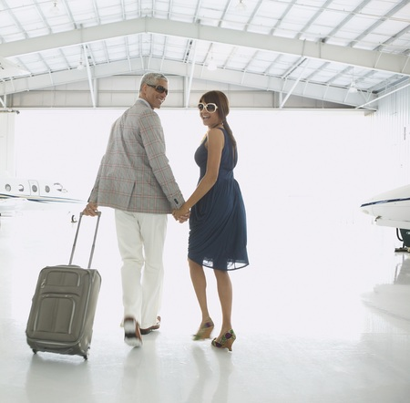 Couple walking out of airplane hanger, Nobato, California, United States LANG_EVOIMAGES