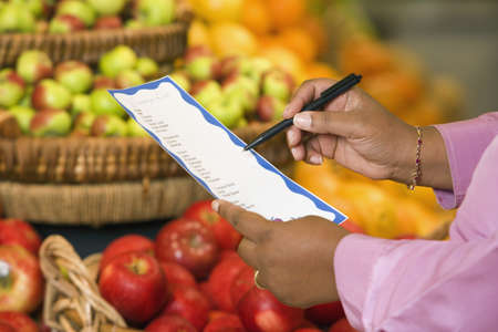 Womans hands with grocery list in produce department LANG_EVOIMAGES
