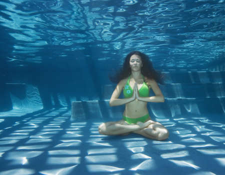 Young woman meditating underwater LANG_EVOIMAGES