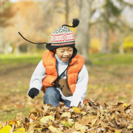 Young Asian child in hat and coat playing in the leaves, Toronto, Canada