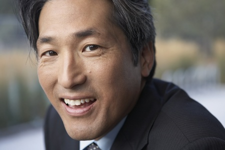 Close up of Asian businessman smiling LANG_EVOIMAGES