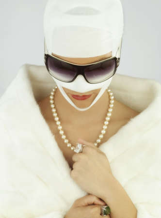 Woman wearing jewelry and plastic surgery bandages