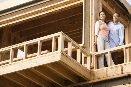 Portrait of Hispanic couple on balcony at construction site LANG_EVOIMAGES