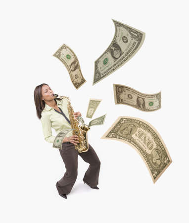 Studio shot of woman playing saxophone with dollar bills coming out LANG_EVOIMAGES