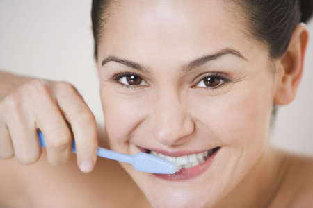 Close up studio shot of Hispanic woman brushing her teeth LANG_EVOIMAGES