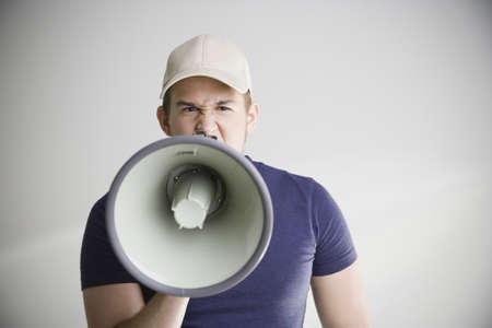 Man wearing baseball hat and yelling into megaphone