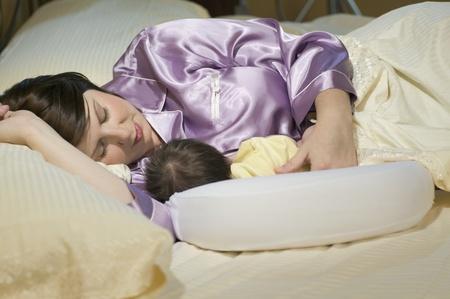 Woman sleeping with newborn baby