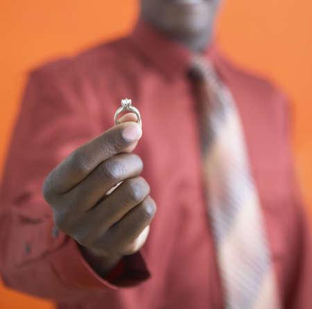 African man holding up diamond ring