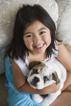 High angle view of young Asian girl holding puppy LANG_EVOIMAGES