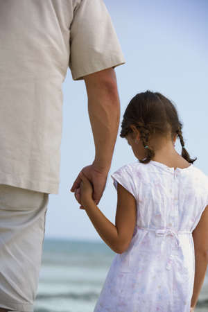 Hispanic father and daughter holding hands at beach LANG_EVOIMAGES