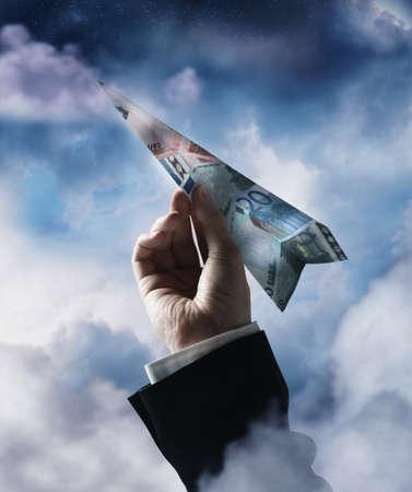 Businessmans hand holding airplane made of Euros