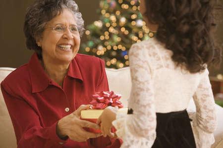 Hispanic granddaughter giving grandmother Christmas gift