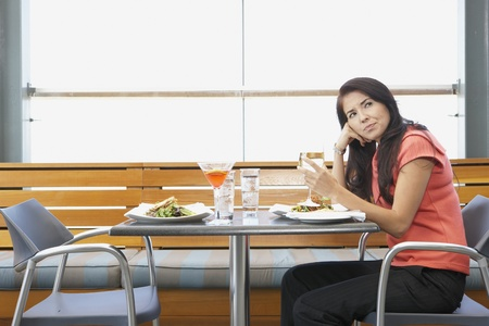 Asian woman waiting at restaurant table