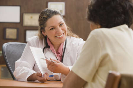 Hispanic female doctor talking to patient in office