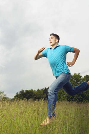 Young man running barefoot in meadow