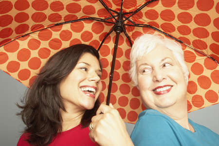 Mother and adult daughter smiling and holding polka dot umbrella