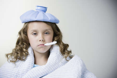 Sick Hispanic girl with thermometer in mouth LANG_EVOIMAGES