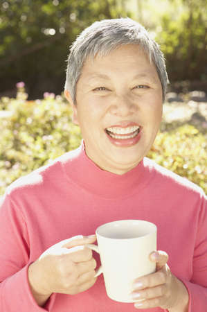 Senior Asian woman sitting in the sunlight drinking tea, San Rafael, California, United States