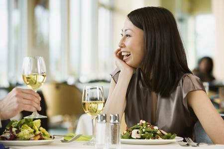 Asian woman laughing at restaurant