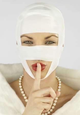 Woman with plastic surgery bandages with finger up to lips LANG_EVOIMAGES
