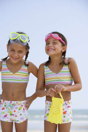 Hispanic sisters wearing matching bathing suits LANG_EVOIMAGES