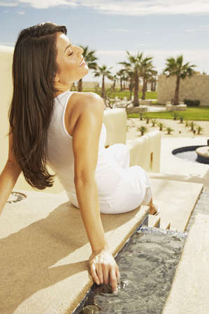 Woman sitting in the sunlight at resort hotel, Los Cabos, Mexico