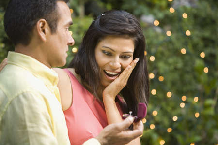 Hispanic man giving girlfriend engagement ring