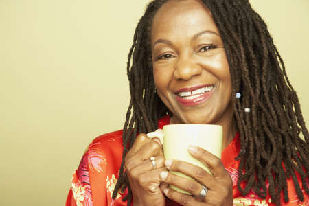 Middle-aged African woman holding coffee mug LANG_EVOIMAGES