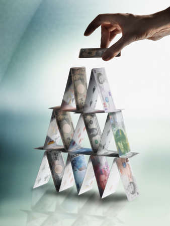 Mans hand making pyramid with world currencies