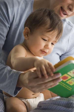 Mother reading Hispanic baby