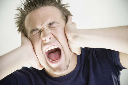 Close up of man yelling and covering ears