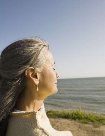 Middle-aged woman with eyes closed next to water LANG_EVOIMAGES