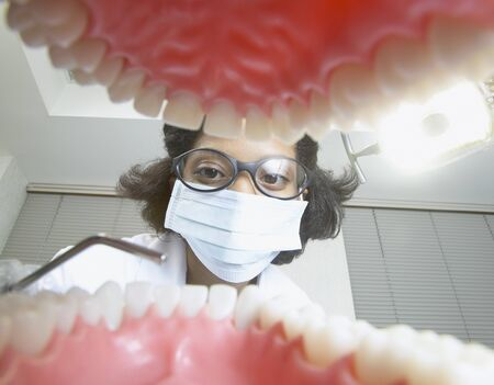 Shot from mouth looking out at African female dentist