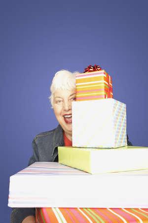 Studio shot of senior woman with stack of gifts