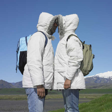 Couple wearing winter jackets and backpacks about to kiss