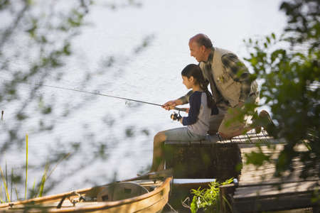 Grandfather and granddaughter fishing on dock LANG_EVOIMAGES