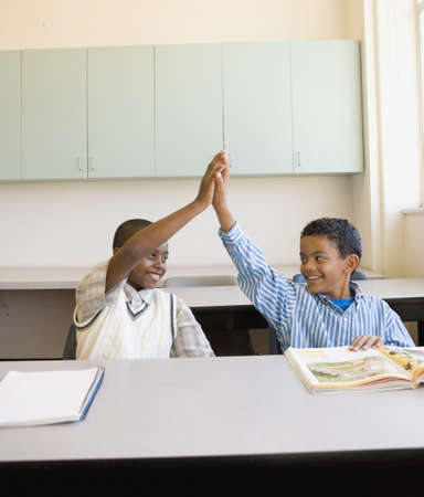 Two young boys high-fiving in classroom