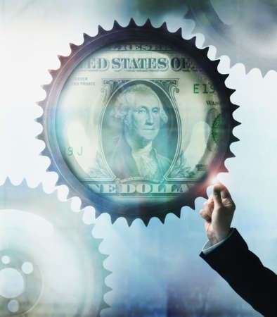 Businessman touching cog wheel with US Dollar in center