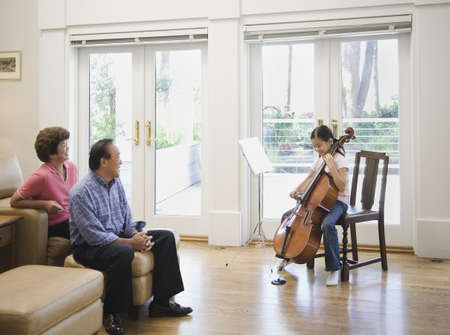 Asian girl playing cello for grandparents