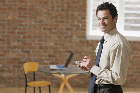 Businessman using PDA indoors LANG_EVOIMAGES