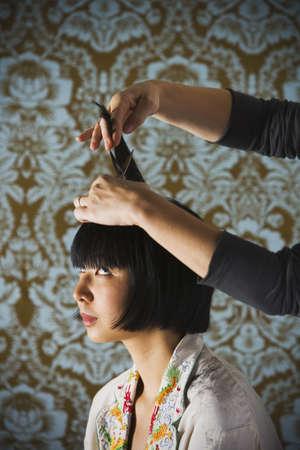 Asian woman getting a haircut
