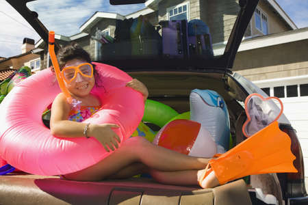 Young girl in beach gear sitting in back of packed car