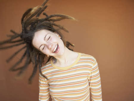 Young woman swinging dreadlocks LANG_EVOIMAGES