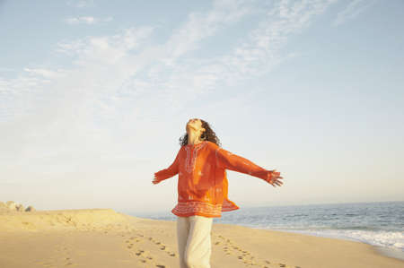Woman with arms outstretched at the beach, Los Cabos, Mexico LANG_EVOIMAGES