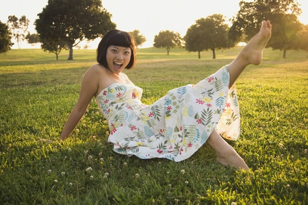 Asian woman kicking up foot in grass
