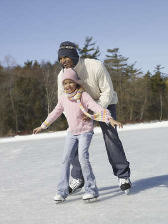 African father and daughter ice skating LANG_EVOIMAGES