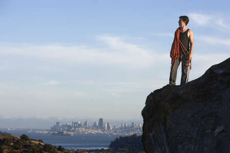 Rock climber with rope on mountain with city in background LANG_EVOIMAGES
