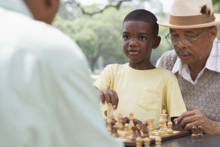 African grandfather and grandson playing chess outdoors LANG_EVOIMAGES