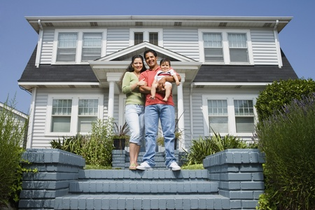 Portrait of Hispanic family in front of house LANG_EVOIMAGES